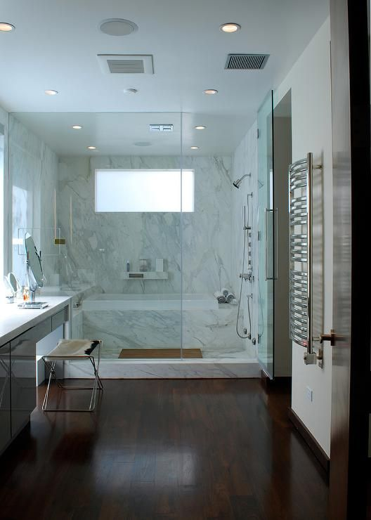 Modern bathroom boasts a seamless glass walk in shower filled with a marble clad bathtub placed under a marble floating shelf.