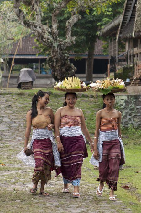 Taken at Desa Tenganan (Tenganan Village), Karang Asem, Bali, Indonesia. Three humble balinese girls walking through pass me with with food on their head.  Photo by rudi gunawan