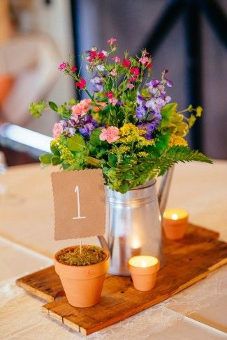 wild flower wedding reception centerpiece using tin watering can and terracotta pots
