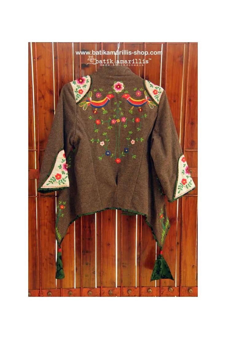 Batik Amarillis's Arcana embroidery jacket Stand out in the crowd with this unique and stunning military cropped inspired jacket,this contemporary and yet vintage style is accented with exquisite embroidery on the shoulders epaulettes ,sleeves & chest adornments also features our triangle arcana tassels to complete the whole extravangant work of art!. material :beautiful hungarian embroidery on cotton-twill with batik gedog Tuban piping