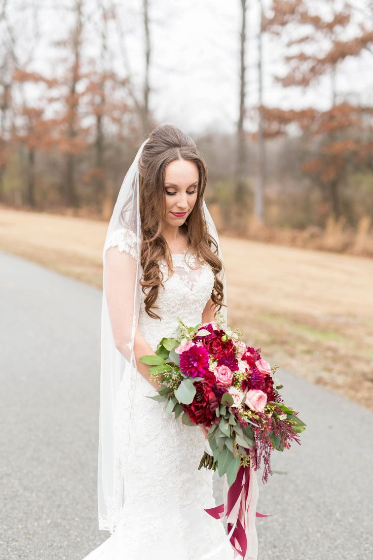 White waltz-length veil, long curly bridal hair, traditional lace wedding dress, red and pink floral wedding bouquets // Reid & Brittany Photography