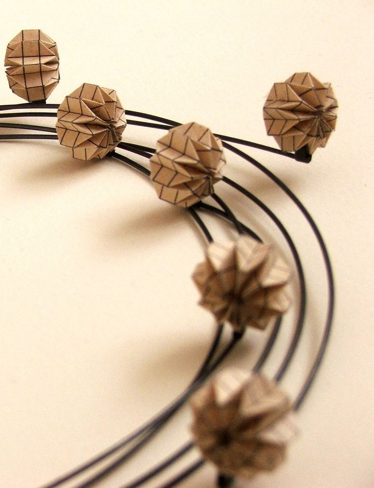 Leila Batten - An origami inspired necklace formed from folded brown paper balls combined with oxidised silver wire.