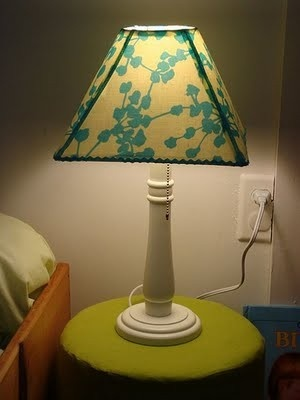 Stiffen fabric with Mod Podge, cut to fit surface, and decoupage over original lamp shade.