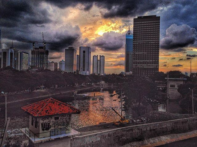 ..and the sunset gave way to the dark clouds. #sunset #orange #sundown #afternoon #darksky #sky #cloudy #cloud #dusktime #earlyevening #buildings #city #yellowhouse #redroof #jakarta #indonesia