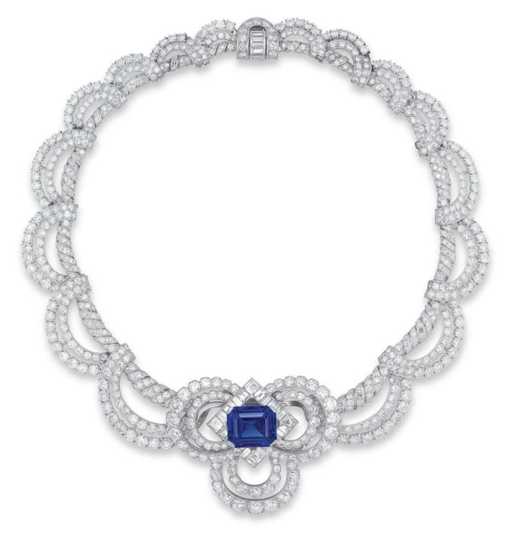 A SAPPHIRE AND DIAMOND NECKLACE/BROOCH, BY CARTIER  DESIGNED AS A SCROLLING NECKCHAIN OF BRILLIANT AND SINGLE-CUT DIAMONDS ALTERNATING WITH SQUARE AND BAGUETTE-CUT DIAMONDS, SUSPENDING A SCALLOPED FRINGE OF BRILLIANT-CUT DIAMONDS, THE FRONT SET WITH A DETACHABLE BROOCH, CENTERING UPON AN OCTAGONAL-SHAPED SAPPHIRE WEIGHING APPROXIMATELY 17.95 CARATS, WITHIN A SQUARE AND BAGUETTE-CUT DIAMOND LOZENGE SHAPE BORDER AND TWO-TIERED BRILLIANT-CUT DIAMOND TREFOIL SURROUND,  MOUNTED IN PLATINUM