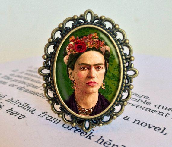 «Pies, ¿lo que necesito para cuando tengo alas para volar?  Frida Kahlo, el más colorido icono feminista, es la reina de la selfie. Frida nos puede enseñar una cosa o dos sobre el poder de joyería y ropa para decorar y proteger. Añadir un broche de Frida a su armadura.  Cada broche es individualmente a mano por encargo en mi estudio en Victoria, Australia. La imagen impresa de alta calidad de Frida es protegida y realzada por una cúpula de cristal. Hay dos estilos disponibles, plata antigua…