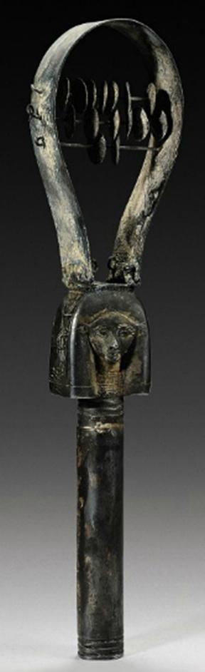 Un antiguo sistro de plata con forma de  la cabeza de la diosa Hathor, con orejas de vaca, cada lado la peluca con una incisión con un uraeus, uno con la corona del Alto Egipto, el otro llevaba corona del Bajo Egipto.