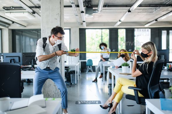 Young People With Face Masks Back At Work In Office After Lockdown