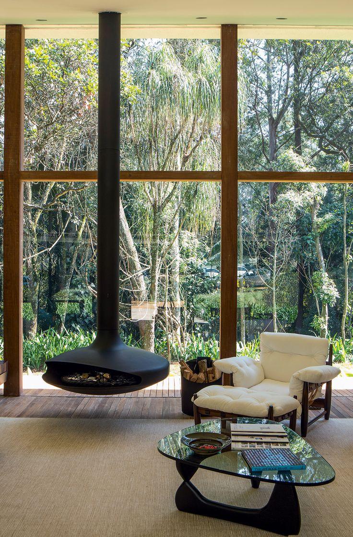 Espaço interno do lounge, projetado por Isay Weinfeld, com panos de vidro. A poltrona Mole, de Sergio Rodrigues, faz par com a mesa de centro de Isamu Noguchi.