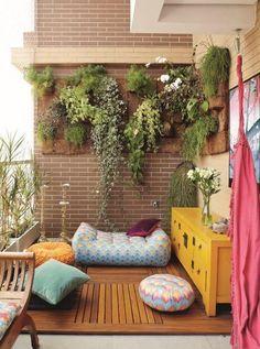 Um deck só no canto da varanda, com muitos pufes, almofadas e, é claro, a parede verde: