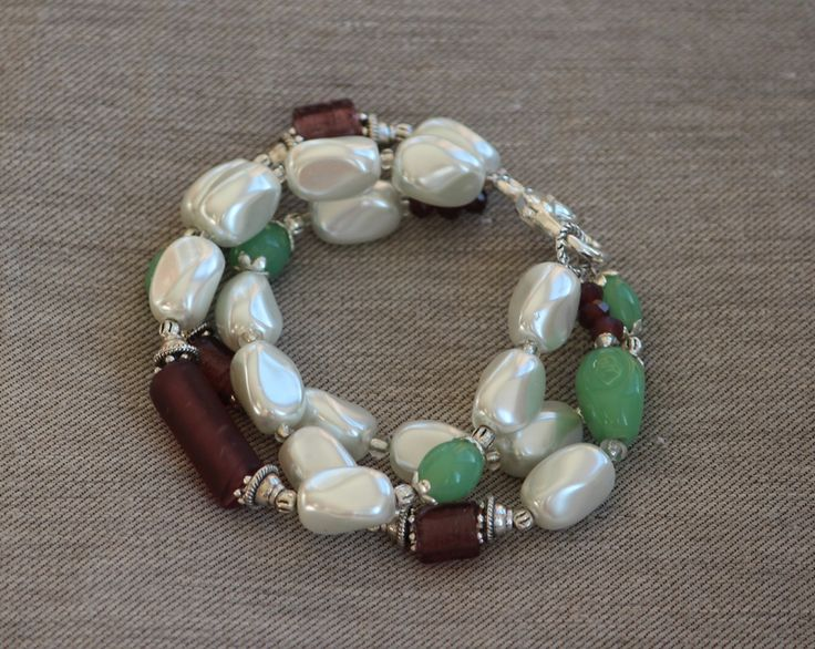 Beaded White multi strand bracelet with green and purple made by HeartBeads.    https://www.facebook.com/heartbeadsjewellery