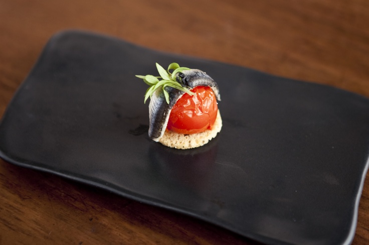 Boquerones. A simple tapa of white anchovy served over roasted tomato with micro herbs and a slivered crouton.