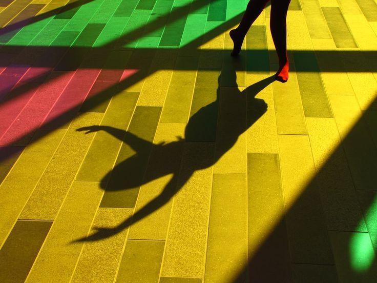 the ballerina casts her shadow on the floor .