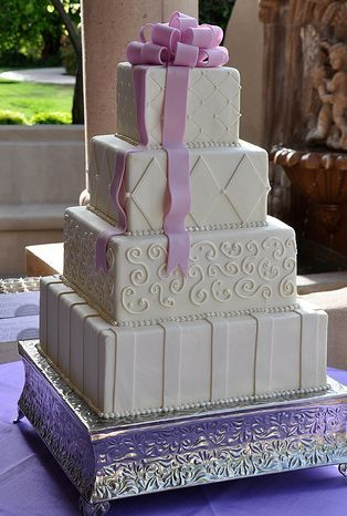 Four tier ivory square wedding cake with lavender bow.JPG