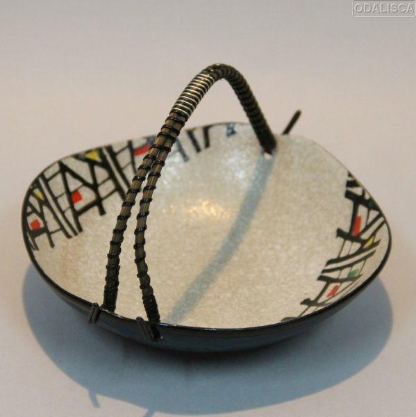 Realizado en cerámica esmaltada con un asa en caña o mimbre con metal plateado y plástico.