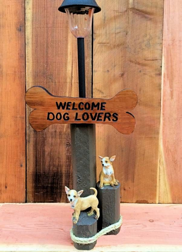 Solar Light Designs are handcrafted from landscaping timber for weather durability and includes a custom-painted sign, solar light and chihuahua figurines.