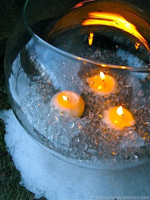 """Glass bowl with polished glass """"pebble"""" ice and candles on a winter evening. Garden Design, Styling & Photography: Michaela Medina - thegardenerseden.com: Fire And Ice Parties Theme, Fire And Ice Centerpieces, Ice Theme Decor, Glasses Bowls Centerpieces, Fire & Ice Theme, Ice Bowls With Candles, Fire And Ice Theme, Fire And Ice Prom Theme Decor, Prom Theme Fire And Ice"""