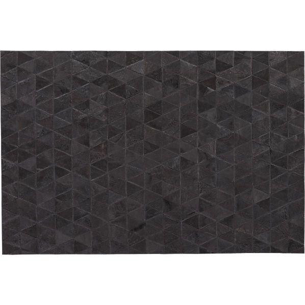 Triangles of 100% black hair-on-hide soft leather stitch together successively in contemporary pattern.
