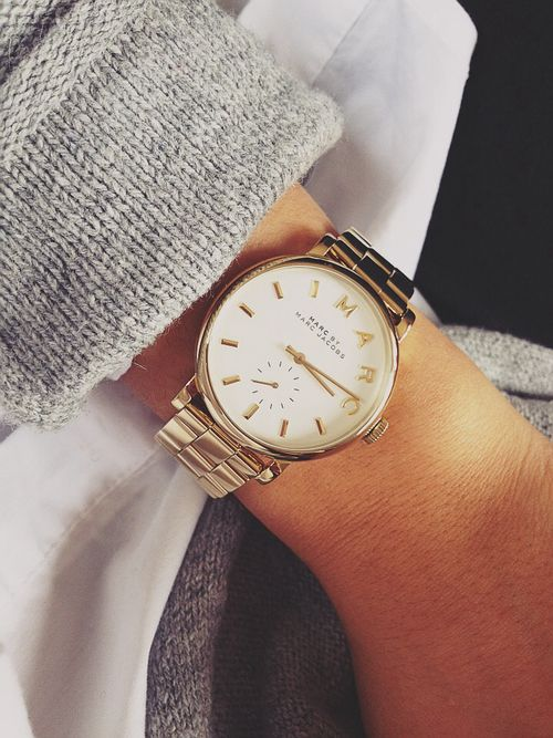 Gold watch and grey sweater.