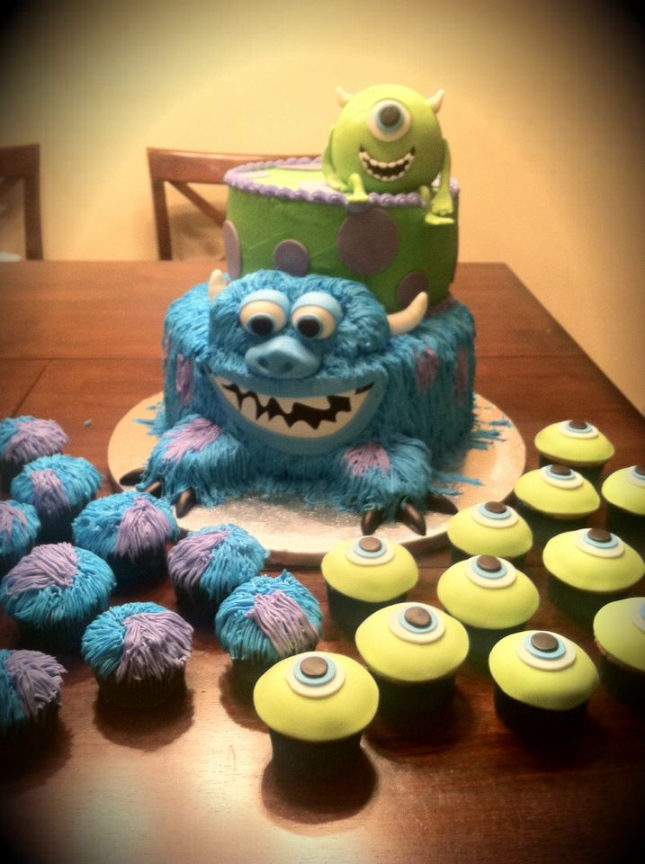 "Another Monsters Inc cake done!! 12"" Sully and a 9"" Mike.. With dozen fondant Mike cupcakes and dozen buttercream Sully cupcakes..."