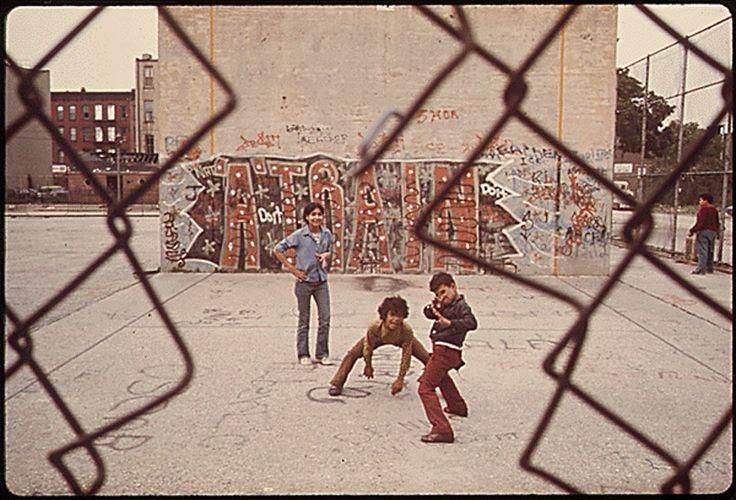 "Three boys and ""A Train"" graffiti in Brooklyn's Lynch Park in New York City. June 1974. Photo by Danny Lyon."