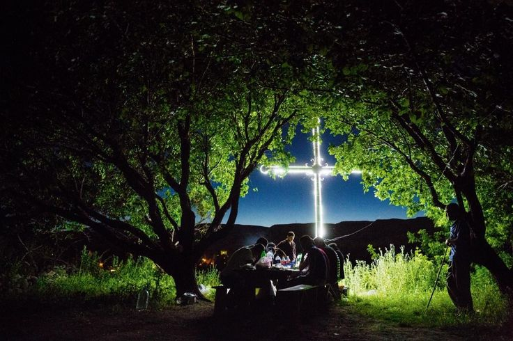 """Villagers in Bagaran, Armenia, sing of cultural endurance and survival while picnicking at night beneath apricot trees—and a giant cross that shines defiantly into Turkey.  This photo was originally published in """"A Century Later, Slaughter Still Haunts Turkey and Armenia,"""" in April 2016.  PHOTOGRAPH BY JOHN STANMEYER"""