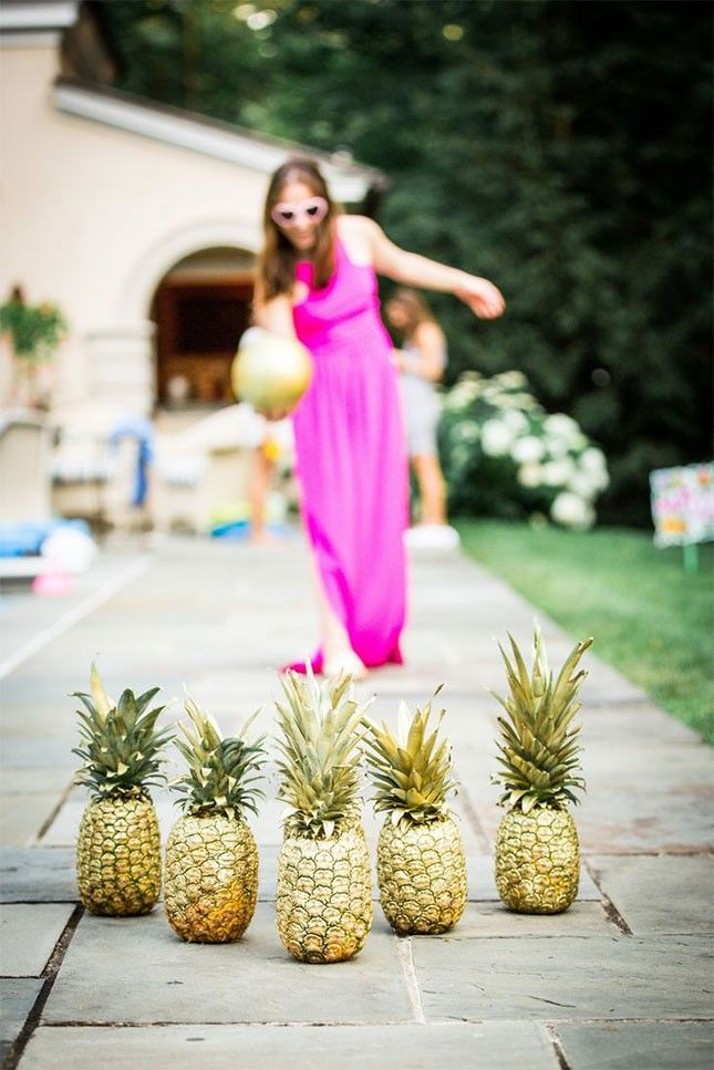 Get creative with your 30th birthday summer pool party decor + make a DIY pineapple bowling set as a fun outdoor lawn game option.