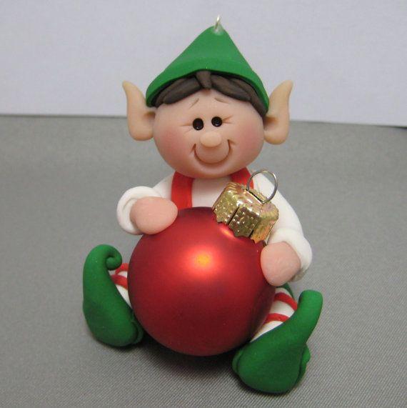 Ce petit lutin est tellement heureuse, agrippant son ornement de Noël. Il a été fait à la main à laide dargile polymère. Il mesure 1.75 et 2 de haut. Il est livré prêt à raccrocher de votre arbre.    Merci pour la recherche