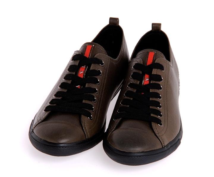 Sneakers basse marroni di Prada con lacci, disponibile in due diversi modelli, uno con lacci tono su tono e l'altro con lacci neri.