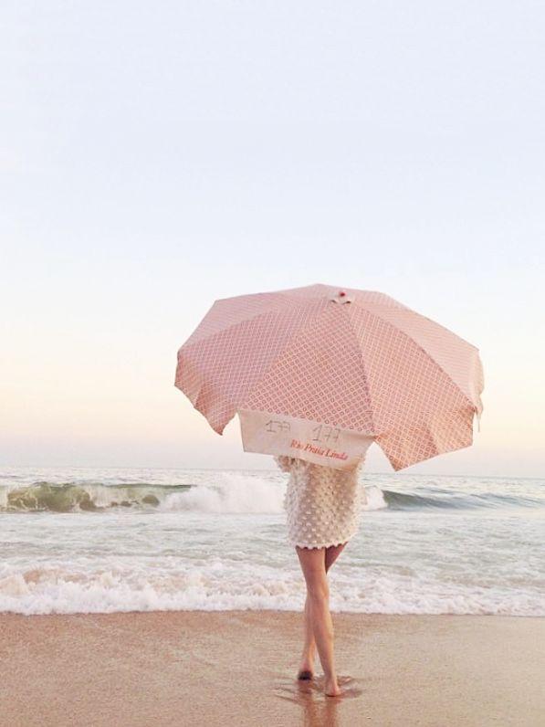 Vintage pink polka dot beach umbrella on sand ocean sea in cape cod Hawaii California island paradise in stormy summer