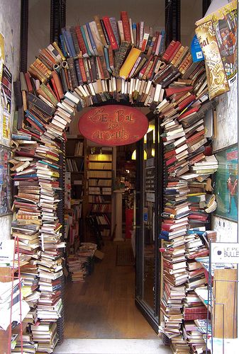 "An arch made of books forms the entryway into the bookshop ""Le Bal des Ardents"" in Lyon, France  (Rue Neuve)  (by Noel Joyeux)"