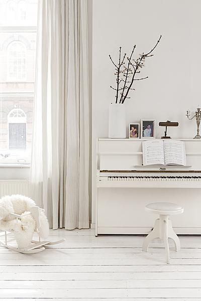 In this white interior is the piano a real eye catcher. The white soft curtains avoid a sterile look.