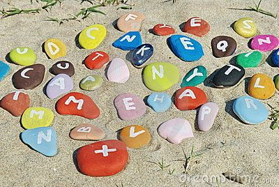 Colourful letters on stones with background of sand