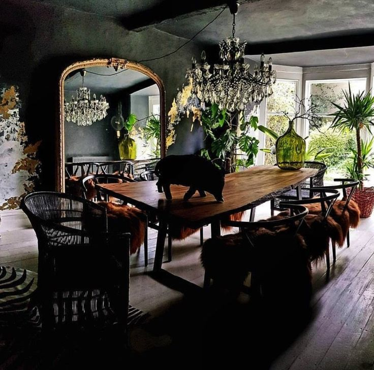 a black dining room with chandelier and large living edge table