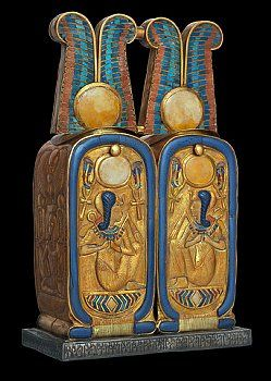 Double container in shape of double cartouche from tomb of Tutankhamun  Double container-gold with inlays of carnelian and colored glass takes the form of two cartouches shaped elements mounted on a flat base of silver. Sun disks flanked by ostrich plumes that signify ma'at the proper order of the universe top each container. Each of the four cartouches thus created contains decoration with cryptographic writings of the king's throne name Nebkheperure. | Located in: Egyptian Museum, Cairo.