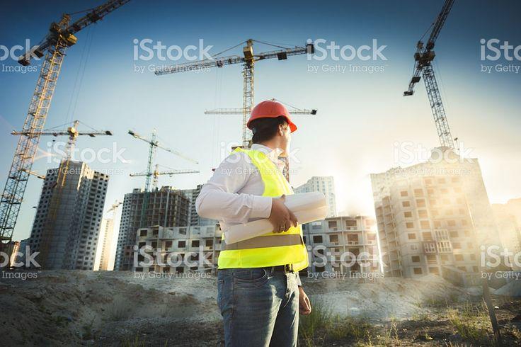 男性のヘルメットとグリーンのジャケットでポーズを取るサイトの構築 ロイヤリティフリーストックフォト