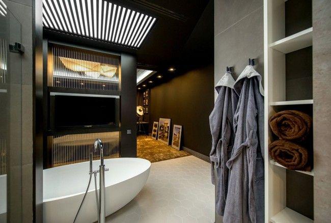 Térben álló fürdőkád egy sötétbarna nappalival