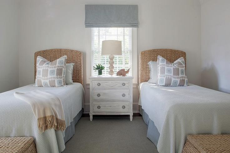 Beige and blue bedroom features two seagrass headboards on twin beds dressed in beige and blue ikat pillows and a blue pleated bedskirt flanking a shared whitewashed nightstand and a beige stacked balls lamp placed under a window covered in a blue roman shade.