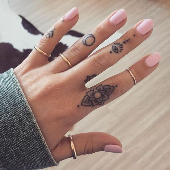 tatuajes-pequeños-en-los-dedos-de-una-mujer-flor-ojo-la-luna-uñas-pintadas