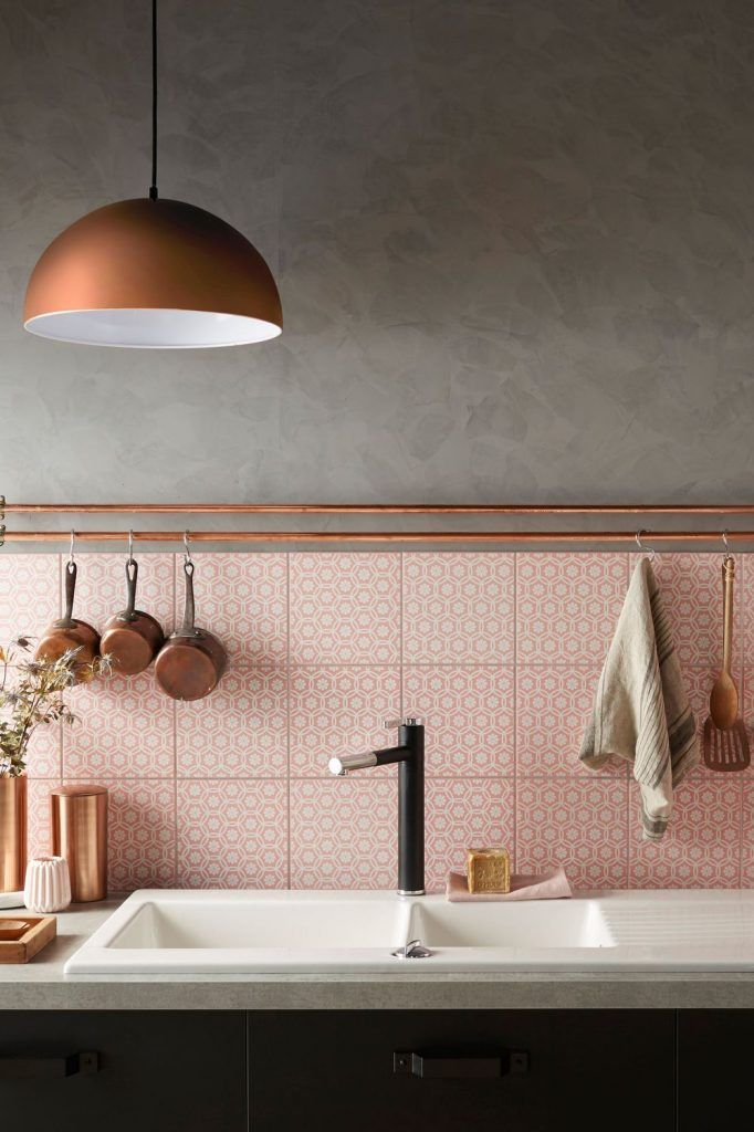 Black kitchen with pink tiles and copper accents