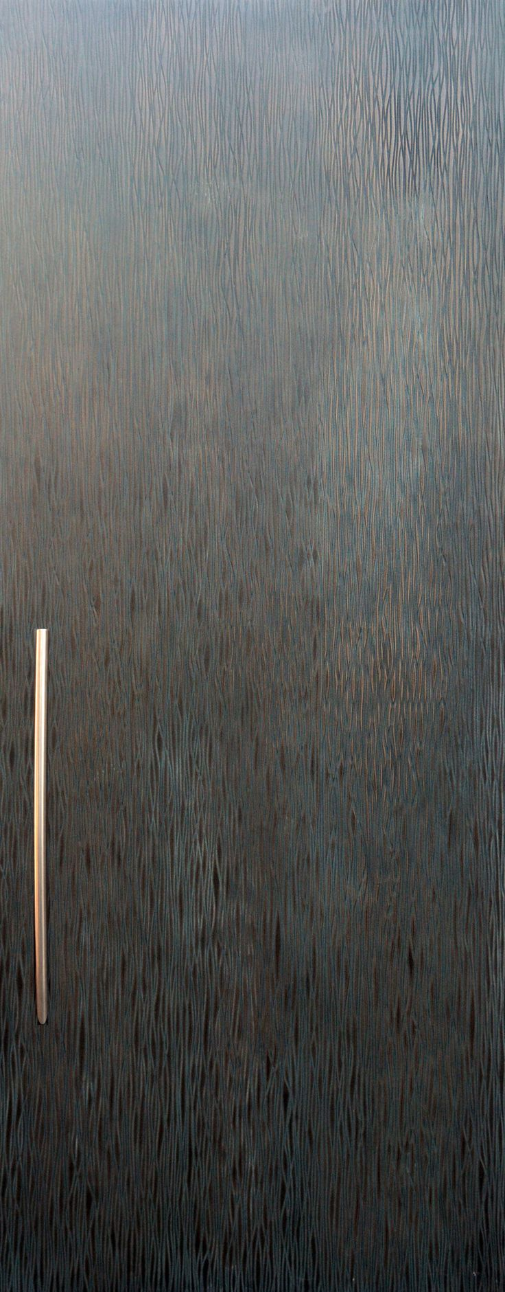 Close-up of distressed bronze door made by Axolotl. We love the texture and rawness of this material treatment.