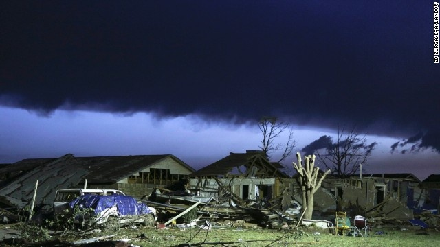 As dawn breaks, storm clouds roll in over a devastated neighborhood on Tuesday, May 21, after a massive tornado ripped through Moore, Oklahoma, on Monday. The death toll continues to climb as rescuers search for survivors. The tornado was estimated to be at least two miles wide at one point as it moved through Moore, in the southern part of the Oklahoma City metropolitan area