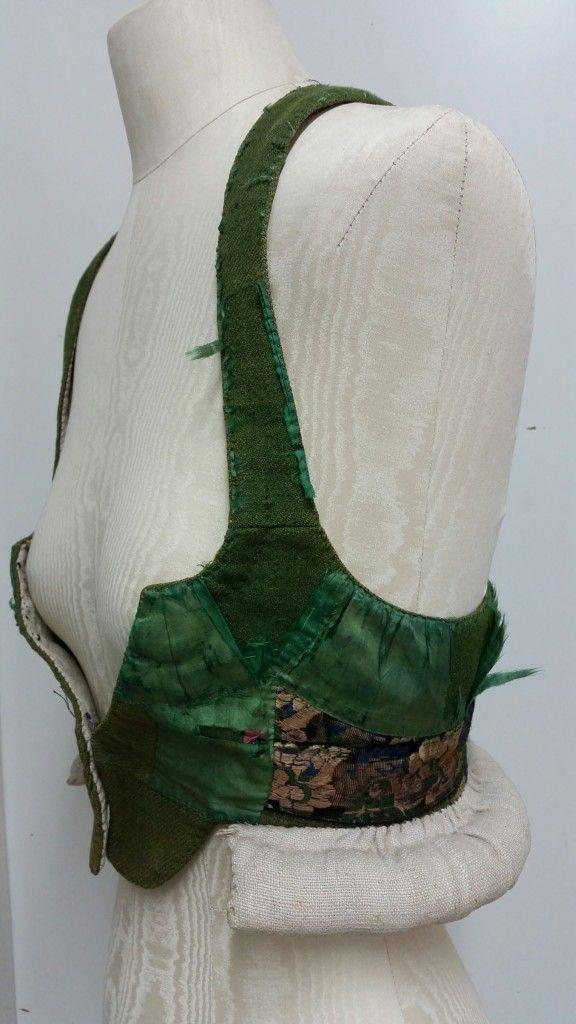 Oxie/Skytts/Vemmenhög. Liv nr 5776 b. Det är sytt av kyprat grönt ylle, har blommiga band som sytts ihop och syns i sidorna och mitt bak under nacken. Det har även dekor av 5,5 cm brett sidentaftband som täcker det mesta av livet. De förekommer i olika material t.ex. sidenbrokad, sammet och ylle som kunde dekoreras med sidenband.