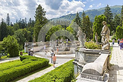 View of Peles castle garden with unidentified tourists strolling down the alleys on a sunny day on July 24, 2013 in Sinaia, Romania. Peles castle was declared museum in 1953 and is the most visited in Romania with more than 300.000 tourists every year.