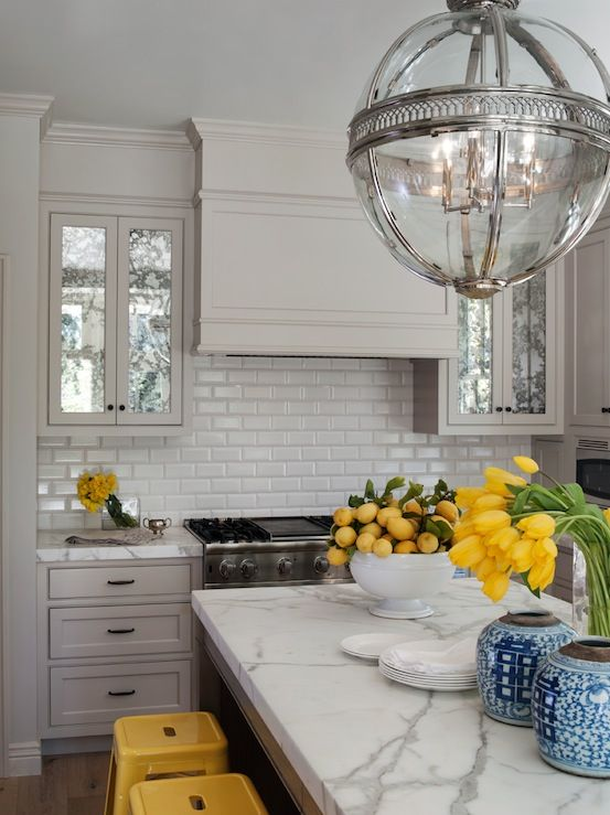 Gorgeous yellow & gray kitchen design with soft gray kitchen cabinets, beveled white subway tiles backsplash, marble countertops, bright yellow Tolix Counter Stools and Restoration Hardware Victorian Hotel Pendant Polished Nickel.