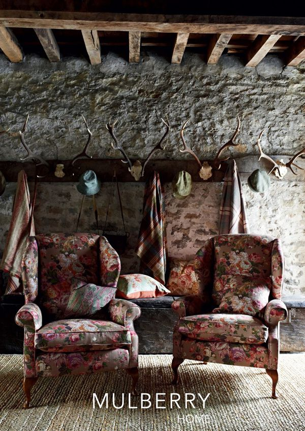 True cosiness and comfort. The colourful mulberry fabrics look glorious against the rustic brick and exposed wooden beams here. We'd love to see roaring candles and lanterns light up this delightful snug on a cosy autumn evening. #floral #fabric #upholstery #countryhouse