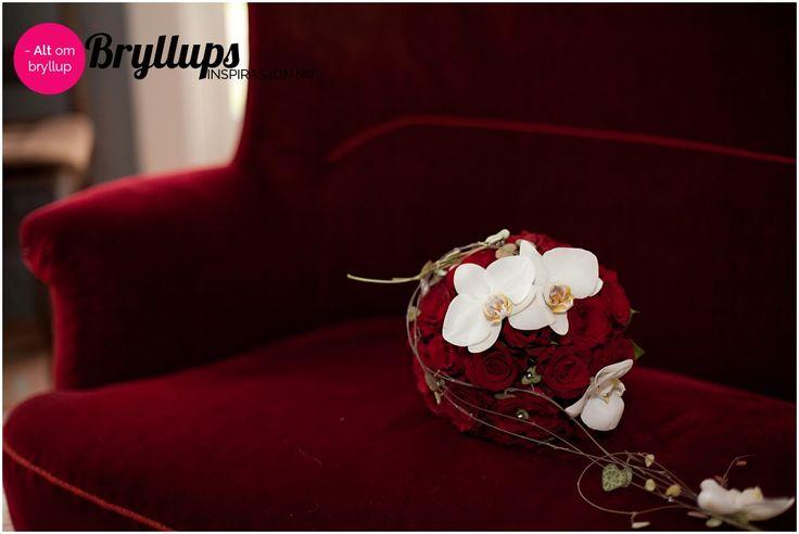 Rund brudebukett i rødt og hvitt med hengende blomster.