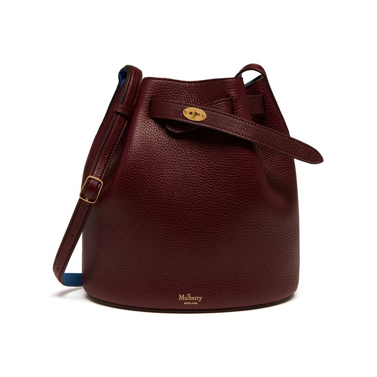 Shop the Abbey in Oxblood & Porcelain Blue Small Classic Grain Leather at Mulberry.com. The Abbey is a traditional 'bucket bag' with drawstring detailing, contrast lining and a range of eye-catching or iconic leather finishes. The Abbey features the iconic postman's lock as a nod to Mulberry's heritage DNA, securing a simple belt closure on a timeless, easy to wear style.