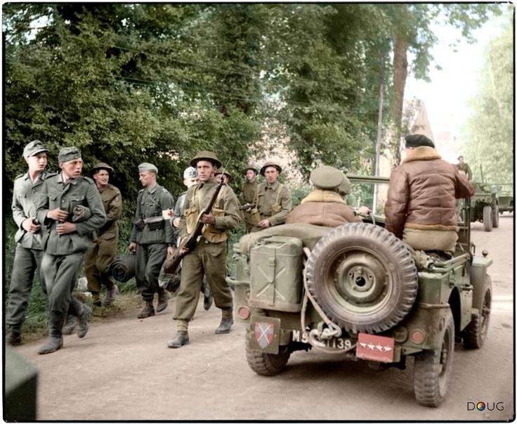 General Sir Bernard Montgomery passes German POWs while being driven along a road in a jeep, shortly after arriving in Normandy, 8th of June 1944.