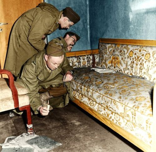 Soviet soldiers examine the bloodstained couch in the Führerbunker where Hitler shot himself, Berlin, 1945